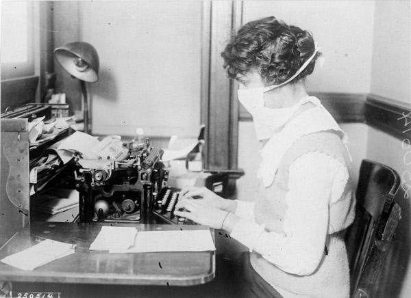 Typist wearing mask, New York City, October 16, 1918 (NARA record 165-WW-269B-16)