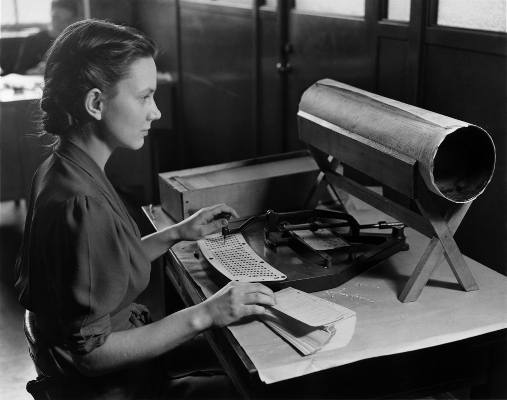 Black and white photo of a woman using a keypunch to tabulate the United States Census, circa 1940.